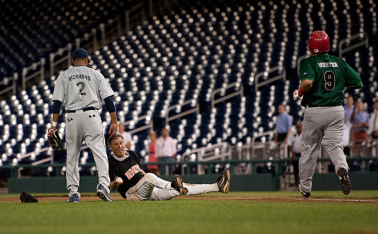 UNITED STATES - JULY 14: First baseman John Carney, D-Del., makes the last play of the game as pitcher Rep. Cedric Richmond, D-La., and batter Rep. Bill Shuster, R-Pa., look on during the 50th Annual Roll Call Congressional Baseball Game held at Nationals Stadium, July 14, 2011.(Photo By Scott J. Ferrell/Roll Call)