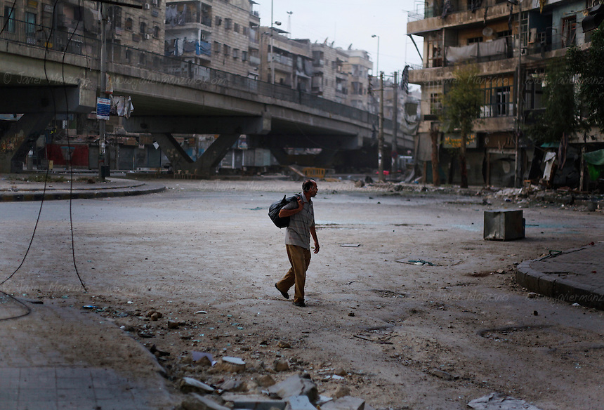 A man walks on an almost deserted street a the battered neighborhood of Sha'ar in the heart of Aleppo city on Tuesday, October 9, 2012. ..© Javier Manzano..