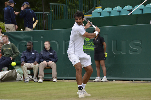 22.06.2013. Stoke park, Slouogh, berkshire, England. The Boodles Challenge mens doubles finals. Jamie Delgado of Great Britain and his American partner James Cerrentani versus the pairing of Adil Shamasolin and Rameez Junaid. Shamasolin with a backhand return