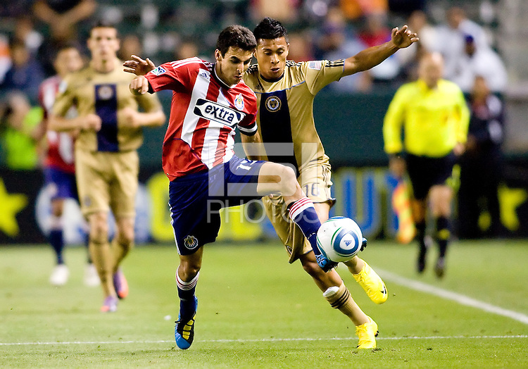 CD Chivas USA's midfielder Jonathan Bornstein (13) moves past Philadelphia Union midfielder Michael Orozco (16) heads a ball over . The Philadelphia Union and CD Chivas USA played to 1-1 draw at Home Depot Center stadium in Carson, California on Saturday evening July 3, 2010..