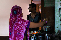 Nitin Jat, 20, helps his mother Lalita Jat, 40, to serve tea in their home in Maheshwar, Khargone, Madhya Pradesh, India on 13 November 2014. Nitin, wants to continue doing Fairtrade cotton farming like the generations before him, but would like to also have a government job in the village so he can have an added source of income. Photo by Suzanne Lee for Fairtrade