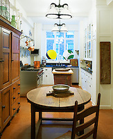 The apartment's kitchen has a country feel with a large wooden dresser, kitchen table and butcher's block