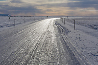 The unpaved James Dalton Highway is purposefully covered with a layer of ice to help maintain the surface integrity, Arctic North Slope, Alaska.