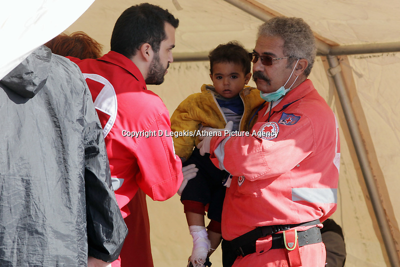 Pictured: Two members of the Red Cross help with a young boy Thursday 27 November 2014<br />