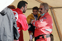 Pictured: Two members of the Red Cross help with a young boy Thursday 27 November 2014<br /> Re: One of the largest refugee boats in recent months has disembarked refugees in Ierapetra, Crete. The freighter Baris, carrying 700 people thought to be from Syria and Afghanistan, is being towed by a Greek frigate.<br /> Officials and Red Cross volunteers prepared an indoor basketball stadium as interim shelter in the southern Cretan port town of Ierapetra on Wednesday ahead of the migrants' expected arrival.<br /> Greek officials said the Baris, which lost propulsion on Tuesday, was being towed slowly in poor sea conditions and would arrive after nightfall, probably early Thursday.<br /> They said it was unclear which Mediterranean location had been the departure point for the 77-meter (254-foot) vessel, which was sailing under the flag of the Pacific nation of Kiribati.
