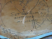 BNPS.co.uk (01202 558833)<br /> Pic: SuzanneHolwell/BNPS<br /> <br /> A signature by Sgt Clark of 414 Bomb Sqn who flew on the historic first flight of American bombers over enemy territory. <br /> <br /> Sections of a torn-down pub ceiling which are covered in 250 signatures from World War Two heroes have been salvaged and turned into a memorial.<br /> <br /> The merry airmen left their mark during raucous evenings at the George and Dragon in the village of Clyst St George in Devon.<br /> <br /> Many of the brave men who signed or drew on the wood ceiling perished in the war in the skies with the Luftwaffe.<br /> <br /> One of them, Sergeant Albert Stilin, of 257 Squadron, was killed aged 21 when he crashed his Hurricane into this pub's roof on September 30, 1942. Another airman later put the initials 'RIP' put after his name.<br /> <br /> The ceiling was taken down in 1975 and half of it was destroyed. <br /> <br /> Robin and Suzannah Holwell recovered the surviving planks from a RAFA association store room in 2009 and have carried out a decade-long preservation project, putting the sections in frames and researching the men behind signatures.