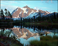 Mount Shuksan reflected at alpine Picture Lake in late afternoon light. Mount Baker Wilderness Area, North Cascades, Washington State.