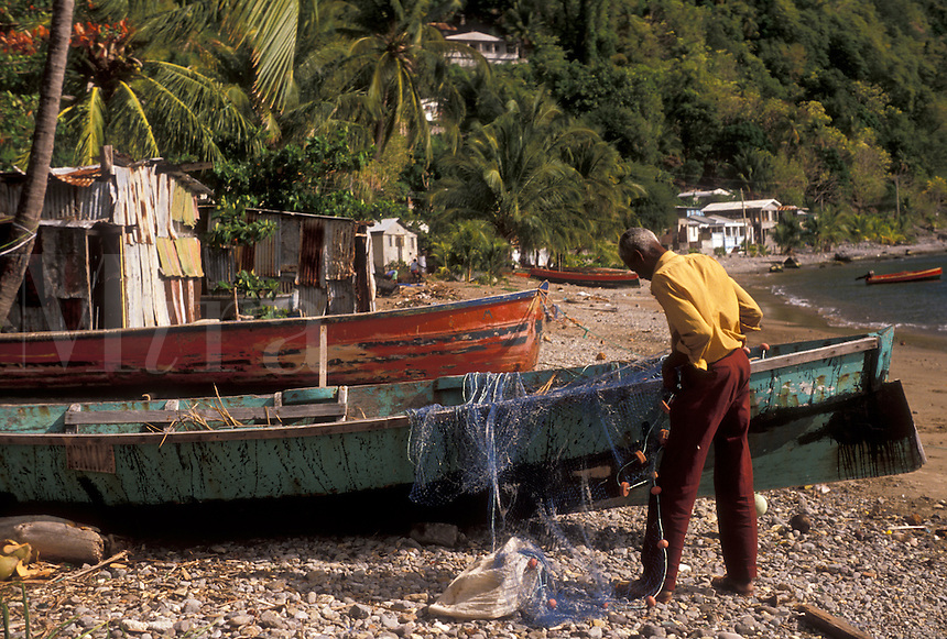 AJ2492, Dominica, Caribbean, Caribbean Islands, Local fishermen working with fishing nets on the beach in Soufriere on the island of Dominica.