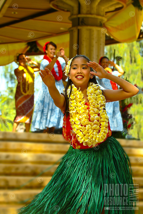 Young hula dancer wearing a grass skirt and plumeria leis at a Lei Day (May 1) auwana (modern or hapa-haole) hula performance at Kapiolani Park, Waikiki Bandstand, Waikiki. Hula is an ancient Hawaiian form of communication.