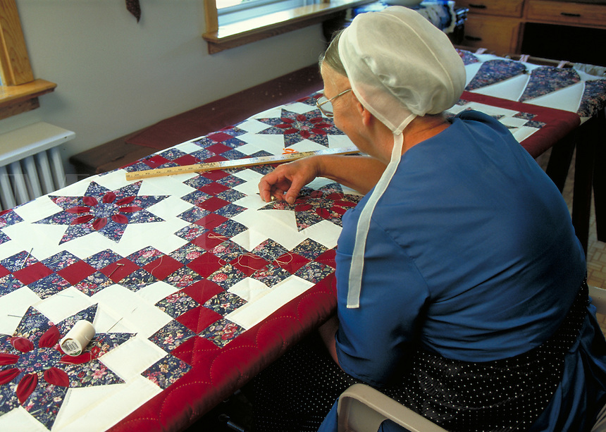 Amish woman quilting a new quilt. Amish woman. Strasburg Pennsylvania USA Lancaster County.