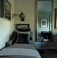 A wall light with a round glass shade hangs over the chaise-longue in a corner of the living room
