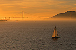 Sailboat in Sanfrancisco Bay at sunset with Golden Gate Bridge in background