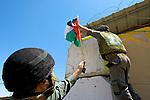 Israeli soldiers remove a Palestinian flag that was placed by demonstrators on an Israeli army watchtower at the entrance to the village of Beit Ummar near Hebron on 05.06.2010. The demonstrators were protesting against the shooting of two boys from the nearby Al 'Arrub refugee camp by an Israeli settler, the Israeli raid on the Mavi Marmara aid ship that resulted in 9 deaths & the blockade of Gaza by Israel & Egypt.