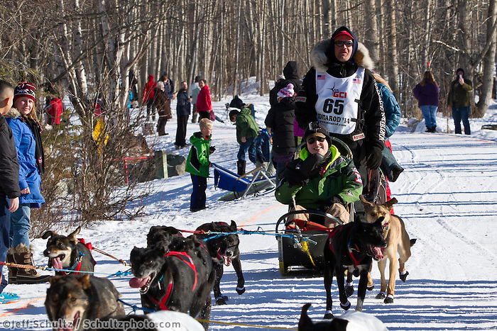 Ken Anderson and team run past spectators on the bike/ski trail during the Anchorage ceremonial start during the 2014 Iditarod race.<br /> Photo by Britt Coon/IditarodPhotos.com