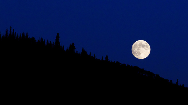 A full moon rises over a mountainside in Steamboat Springs, Colorado.
