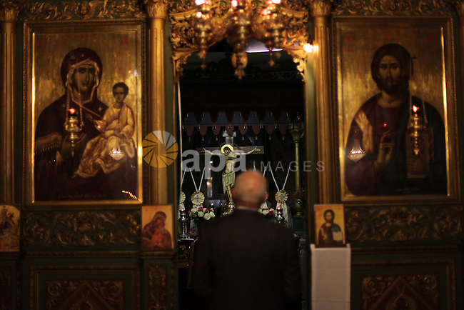Palestinian Greek Orthodox Christians attend Christmas mass at the Orthodox Saint Porfirios church in Gaza City on January 7, 2014. The Orthodox Church celebrates Christmas and other religious holidays according to the Julian calendar, while other Christian churches have adopted the later Gregorian calendar. Photo by Ashraf Amra