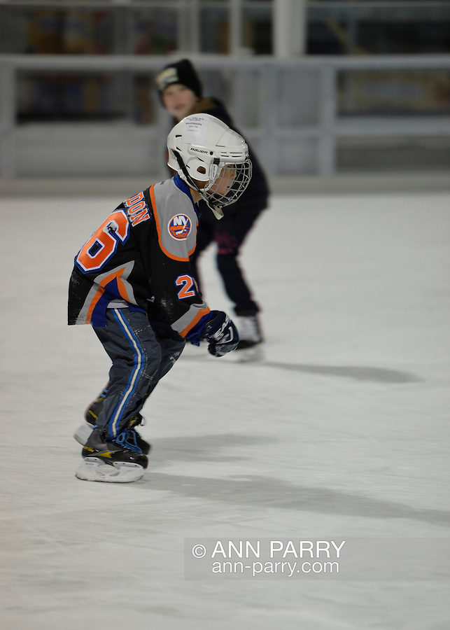 East Meadow, New York, USA. December 31, 2014. Two young boys, one wearing a New York Islanders ice hockey team style shirt, ice skates before runners participate in a 5K New Year's Eve DASH to support the Long Island Council on Alcoholism and Drug Dependence (LICADD) at the Twin RInks Ice Center at Eisenhower Park in Long Island. A Skatin' New Year's Eve event started hours earlier and a New Year's Eve Party, open to runners, family and friends continued until 2:30 a.m.