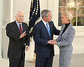 Washington, DC - March 5, 2008 -- United States Senator John McCain (Republican of Arizona), left, the presumptive 2008 Republican nominee for President of the United States waves to the cameras as United States President George W. Bush, center, welcomes McCain's wife, Cindy, right, on the North Portico of the White House on Wednesday, March 5, 2008..Credit: Ron Sachs / CNP