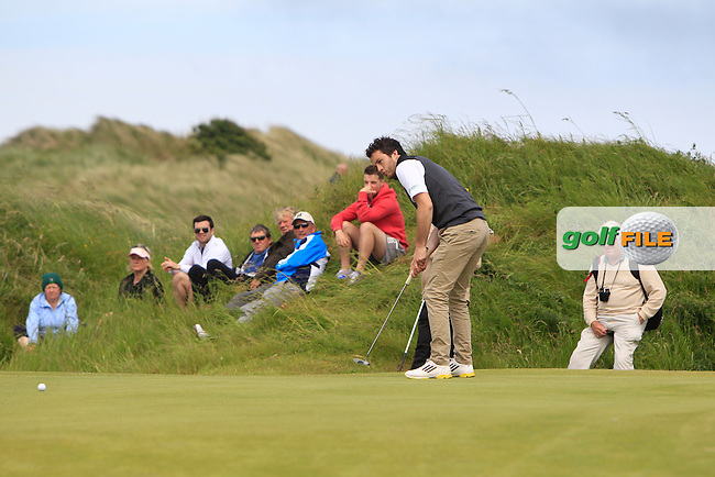 Gerard Dunne (Co. Louth) on the 9th green watched by Des Smyth (Vice-Captain Ryder Cup Team 2014) during Round 4 of the Irish Amateur Close Championship at Seapoint Golf Club on Monday 9th June 2014.<br /> Picture:  Thos Caffrey / www.golffile.ie