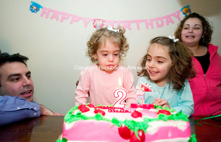 WATERTOWN, CT- 29 DEC 06- 123006JT34- <br /> Alesia Faith Pandiscia looks at the lit candle on her birthday cake as her father Stephen, sister Olivia, 5, and aunt Daniela DiCicco sing &quot;Happy Birthday&quot; at the Pandiscia's Watertown home on Dec. 29, 2006.<br /> Josalee Thrift Republican-American