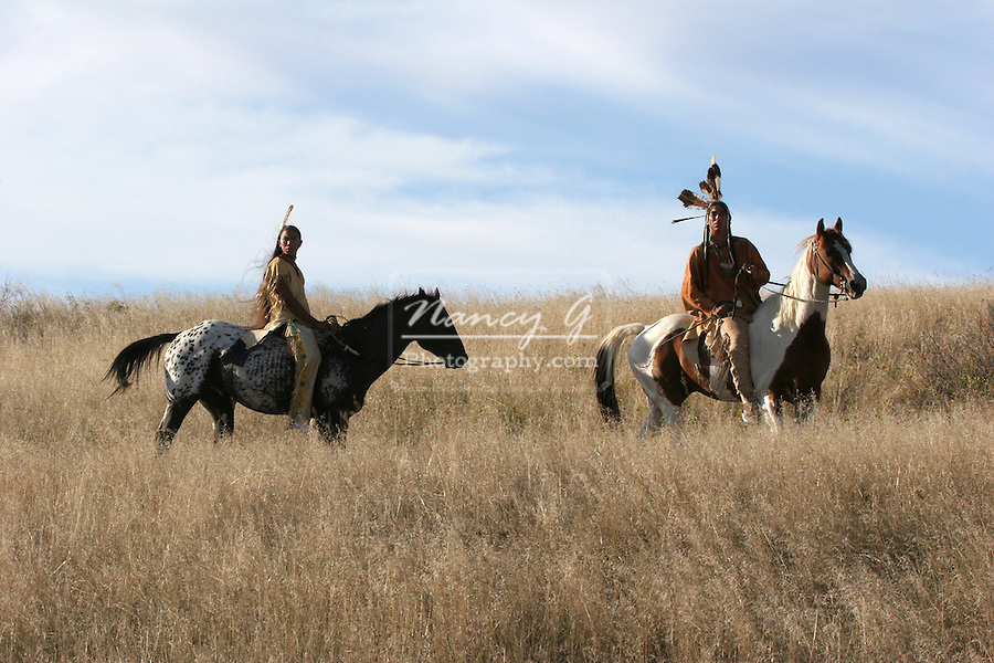 Two Native American Indian men on horseback scouting for enemies or hunting for food in the prairie of South Dakota
