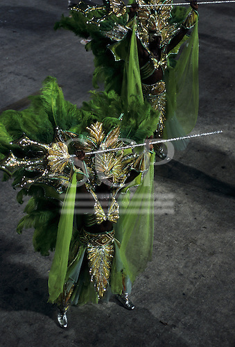 Rio de Janeiro, Brazil. Carnival: samba school passistas in green and gold costumes with tridents.