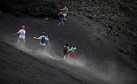 Hikers walk and slide on cooled lava on a trail on Volcan Pacaya in Guatemala.