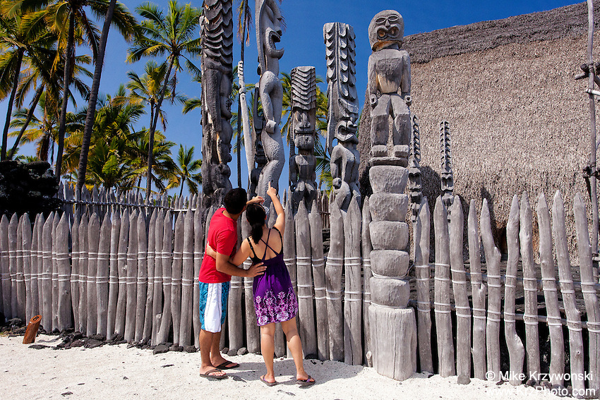 Tourist couple admiring tiki statues in the Puuhonua o Honaunau National Historical Park on the Big Island of Hawaii
