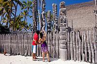 Tourist couple admiring tiki statues in the Puuhonua o Honaunau National Historical Park on the Big Island of Hawaii