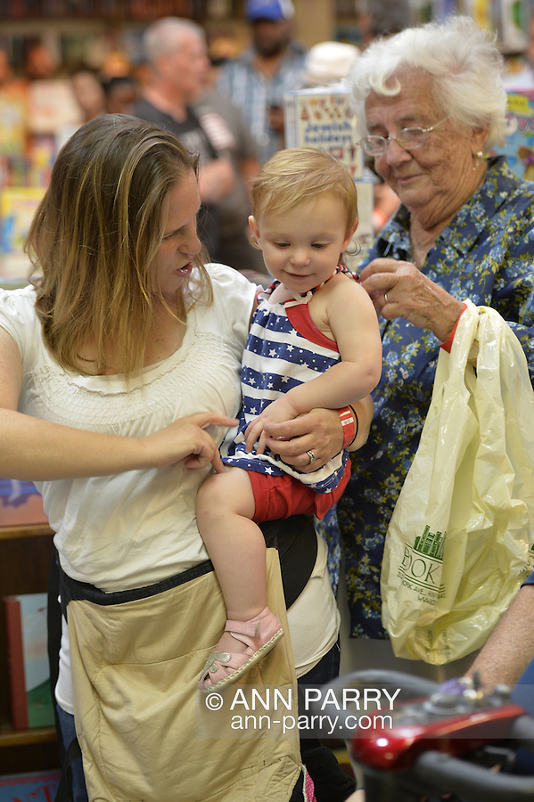 Huntington, New York, U.S. - August 6, 2014 - A young mom holding a baby girl and a senior woman talk while waiting online at the book signing for the H. Clinton new memoir, Hard Choices, at Book Revue in Huntington, Long Island. Clinton's book is about her four years as America's 67th Secretary of State and how they influence her view of the future.