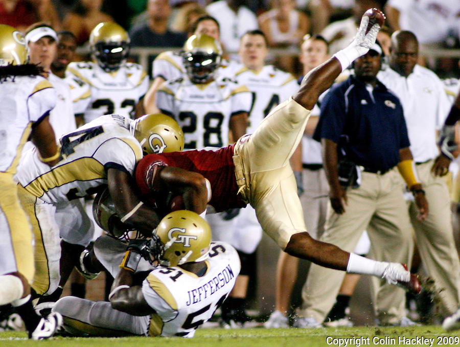 TALLAHASSEE, FL 10/10/09-FSU-Ga. Tech FB09 CH26-Florida State's Jarmon Fortson is caught by Georgia Tech's Sedric Griffin, left, and Brad Jefferson during first half action Saturday at Doak Campbell Stadium in Tallahassee. .COLIN HACKLEY PHOTO