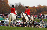 Throngs of spectators fill the infield behind two Huntsman chatting between races Satruday during the Montpelier Hunt Races in Orange, Va. /Andrew Shurtleff