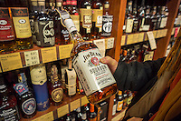 A consumer prepares to purchase a bottle of Jim Beam bourbon in a liquor store in New York on Tuesday, January 14, 2014.  The Japanese company Suntory Holdings has proposed the purchase of Beam Inc., the maker of Jim Beam, Maker's Mark and other liquors, for $16 billion.  Suntory is one of Japan's largest brewers and the purchase, if approved,  would make the company the third largest liquor produce behind Diageo and Pernod Ricard. (© Richard B. Levine)
