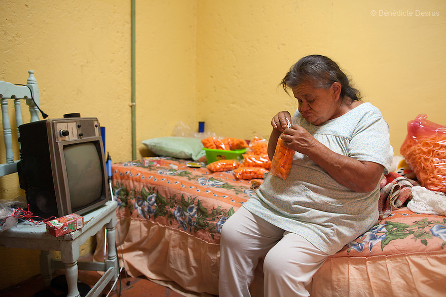 Canela, a resident of Casa Xochiquetzal, in her bedroom at the shelter in Mexico City, Mexico on September 20, 2012. Originally from Oaxaca, she came to Mexico City to work at a very young age. She is well known and respected in the neighborhoods that surround Casa Xochiquetzal. At 72, she suffers a number of illnesses and has Down's syndrome. Of all the women at Casa Xochiquetzal, Canela is the only one who did not have children. Casa Xochiquetzal is a shelter for elderly sex workers in Mexico City. It gives the women refuge, food, health services, a space to learn about their human rights and courses to help them rediscover their self-confidence and deal with traumatic aspects of their lives. Casa Xochiquetzal provides a space to age with dignity for a group of vulnerable women who are often invisible to society at large. It is the only such shelter existing in Latin America. Photo by Bénédicte Desrus