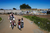 SOWETO, SOUTH AFRICA JANUARY 4: A group of French tourists participate in a Soweto tour on January 4, 2013 in the Meadowlands section of Soweto, South Africa. A local company arranges bicycle tours where tourists can explore the sights, historic places and mix with locals on a bike. Soweto today is a mix of old housing and newly constructed townhouses. A new hungry black middle-class is growing steadily. Many residents work in Johannesburg but the last years many shopping malls have been built, and people are starting to spend their money in Soweto. (Photo by: Per-Anders Pettersson)
