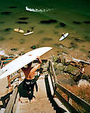 USA, California, Santa Cruz, surfers at Cowell's Surfbreak, going down the stairs off of West Cliff Drive