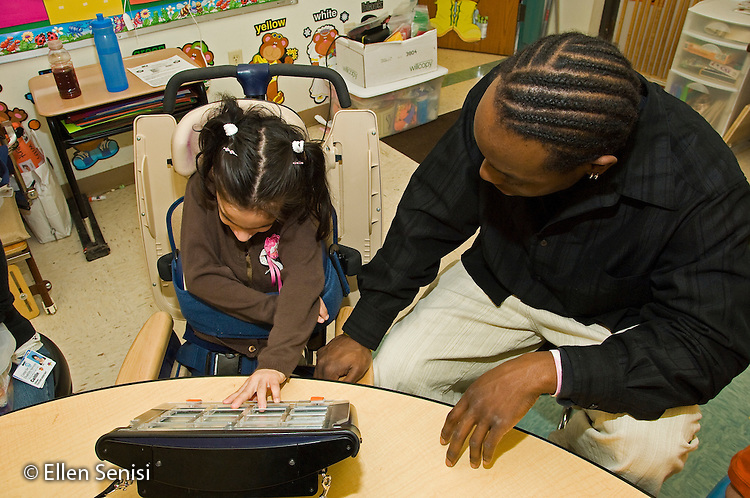 MR / Albany, NY.Langan School at Center for Disability Services .Ungraded private school which serves individuals with multiple disabilities.Teaching assistant (African-American) help a student use an alternative and augmentative communication device during speech and language development lesson. Girl: 7, cerebral palsy, nonverbal with expressive and receptive language delays..MR: Wes2, Del16.© Ellen B. Senisi