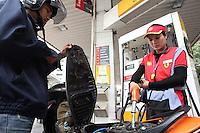 NAR04. BANGKOK (TAILANDIA), 03/03/2011.- Una mujer llena el tanque de una moto hoy, jueves 3 de marzo de 2011, en una estación de servicio en Bangkok, Tailandia, despues de que se anunciara que los comerciantes tailandeses de gasolina buscan aumentar el valor del combustible debido al incremento en el precio mundial del petróleo. EFE/NARONG SANGNAK