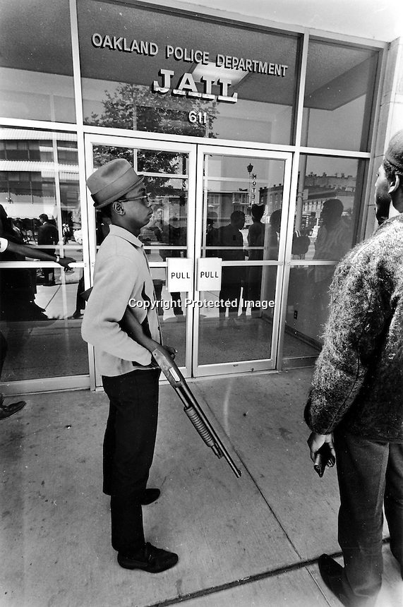 Armed Black Panthers in front of the Oakland California Police Jail. Standing with shot gun is 17 year -old Bobby Hutton who was shot and killed by Oakland Police in a shootout a few months later(1967 photo by Ron Riesterer (copyright@2014