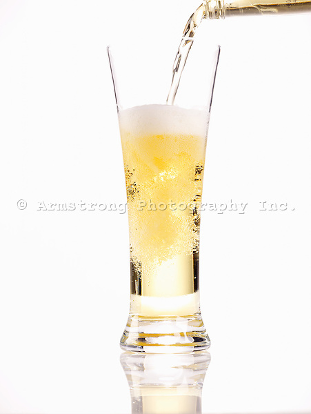 A pale beer being poured from a bottle into a tall pilsner glass. White background