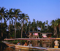 Tourist boat on the Klongs, showing the colourful wooden houses on stilts in Bankok, Thailand