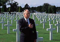 An American veteran stands in salute at the United States military cemetery in Normandy.
