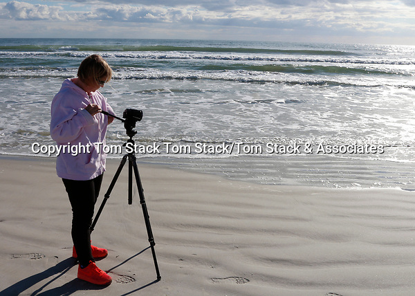 A woman videographer on the Atlantic ocean beach