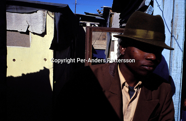 dicuinit00024 Culture. Initiation. Luthando Damiso, age 23, dressed in a suit and hat outside his family's shack on August 10, 2001 in the Site B section in Khayelitsha, a township about 35 kilometers outside Cape Town, South Africa. Luthando has just returned from a rural area in the Eastern Cape province where he has spent one month going trough the traditional Xhosa manhood ceremony. A ceremony done for centuries to prepare boys to go into manhood. The boys are circumcised and taught by elders during their month long stay in a hut in a rural area. He has returned to his family and has to wear these clothes in the township for about six months.  Khayelitsha is one of the poorest and fastest growing townships in South Africa. .Photo: Per-Anders Pettersson/ iAfrika Photos...