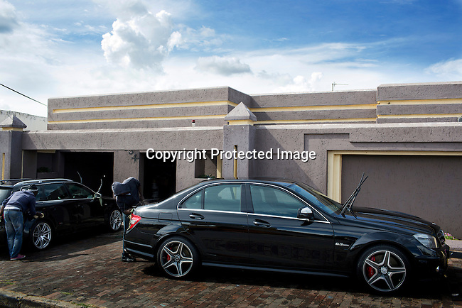 SOWETO, SOUTH AFRICA FEBRUARY 1: Men clean fancy sport cars parked outside an upmarket house on February 1, 2014 in Diepkloof section, Soweto, South Africa. Soweto is a mix of old housing and newly constructed townhouses and upmarket areas such as Diepkloof. The population in Soweto is estimated to be around one million people. A new hungry black middle-class is growing steadily. Many residents work in Johannesburg but the last years many shopping malls have been built, and people are starting to spend their money in Soweto. (Photo by: Per-Anders Pettersson)