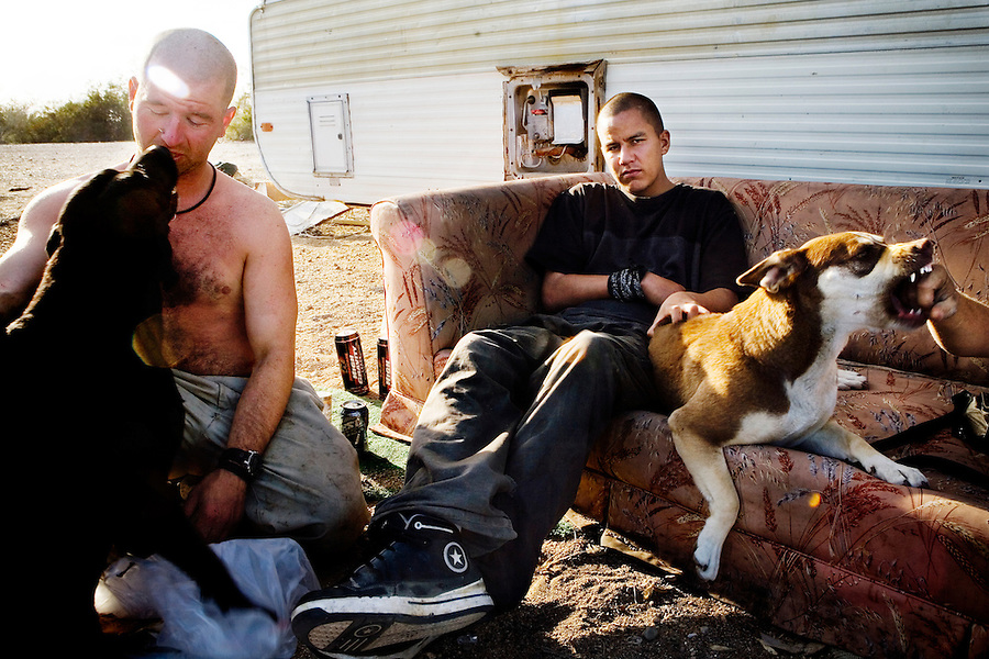 Niland, California, February 19, 2008 - Judd Jones sits on his couch with his dog Coco while best friend Dave Hines kisses his dog, Blackie. Both men suffer from Fetal Alcohol Syndrome and medicate themselves with anything they can find. Today it was malt liquor stolen from the nearby market. Jones was arrested later that day for an outstanding warrant from December when he raped his mother and set her trailer on fire with her in it. She did manage escape..