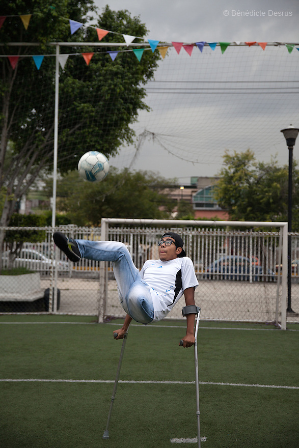 """Baruch uses his crutches to perform an overhead volley during training in Mexico City, Mexico on June 26, 2014. Baruch Alejandro Anleu Ramirez, 18, is the captain of Guerreros Aztecas. Two years ago, Baruch had his left leg amputated due to bone cancer. He used to practice as much as his chemotherapy would allow. Expelled from school for missing too many classes during his treatment, he says, """"Guerreros Aztecas has filled a big hole in my life"""". Baruch was Guerreros Aztecas's brightest hope to represent Mexico at the Amputee Soccer World Cup. But since the cancer's spread to his lungs, he can no longer play or train with the team. Guerreros Aztecas (""""Aztec Warriors"""") is Mexico City's first amputee football team. Founded in July 2013 by five volunteers, they now have 23 players, seven of them have made the national team's shortlist to represent Mexico at this year's Amputee Soccer World Cup in Sinaloathis December.The team trains twice a week for weekend games with other teams. No prostheses are used, so field players missing a lower extremity can only play using crutches. Those missing an upper extremity play as goalkeepers. The teams play six per side with unlimited substitutions. Each half lasts 25 minutes. The causes of the amputations range from accidents to medical interventions – none of which have stopped the Guerreros Aztecas from continuing to play. The players' age, backgrounds and professions cover the full sweep of Mexican society, and they are united by the will to keep their heads held high in a country where discrimination against the disabled remains widespread.(Photo byBénédicte Desrus)"""