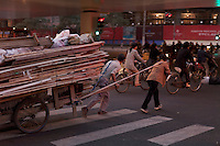 A couple transports building materials on a busy street in Shanghai, China on November 05, 2009.