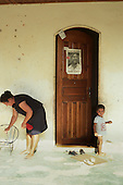 Xapuri, Acre State, Brazil. Woman with her son outside their house with a Chico Mendes poster, shoes and sandals.