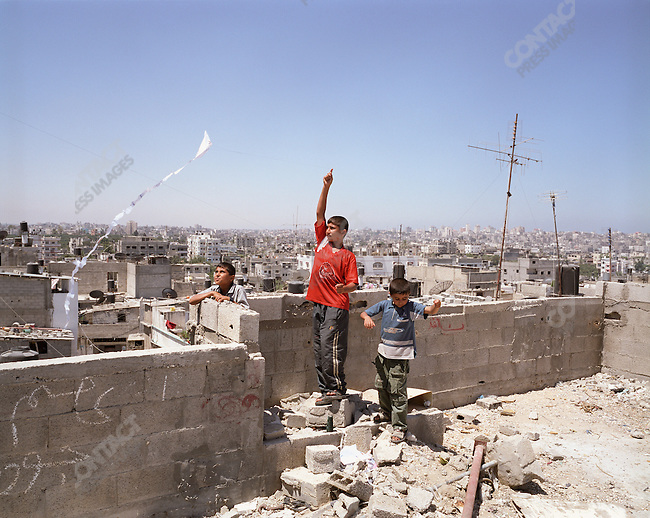 Palestinian boys fly a kite from a rooftop, Jabalia refugee camp, Gaza Strip. July 2005.